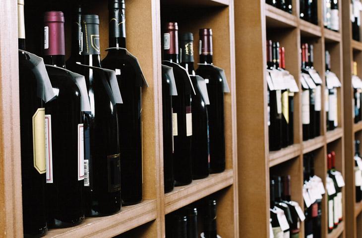 Bottles of wine on shelves in a bottle-store.