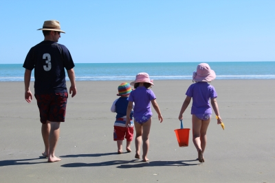 Father and his 3 young children walking to the sea on a beach.