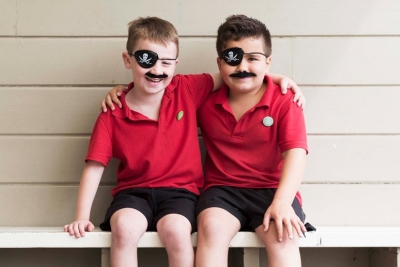 Two primary-school aged boys dressed as pirates with eye-patches and moustaches.