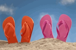 Two pairs of jandals upright in a pile of sand.
