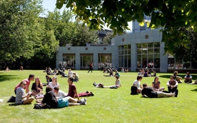 Groups of students sitting on a green space outside a university building. Source: University of Canterbury.
