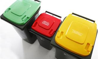 Set of wheelie bins - green for organics, red for rubbish and yellow for recycling.